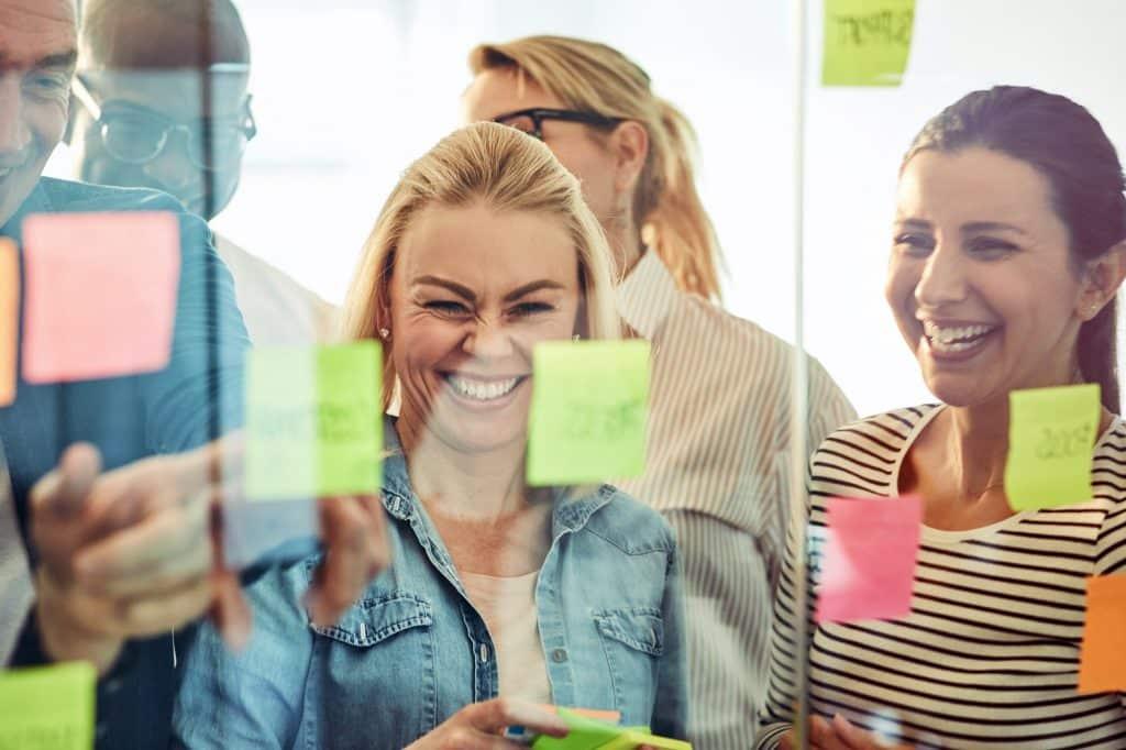 Geschäftsleute lachen beim Brainstorming mit Haftnotizen in einem Büro