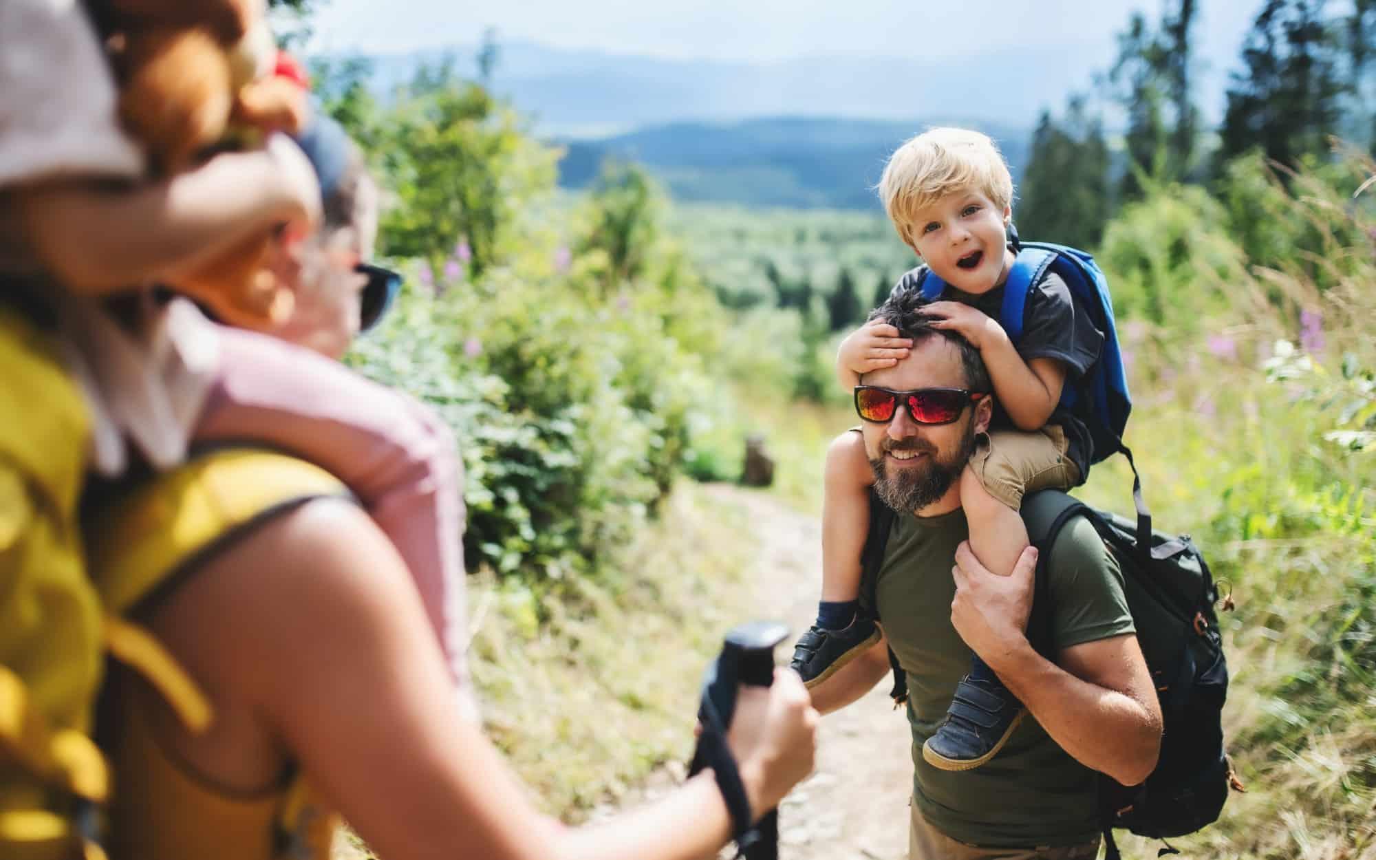 Family with small children hiking outdoors in summer nature
