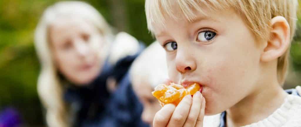 Kleiner Junge isst eine Mandarine