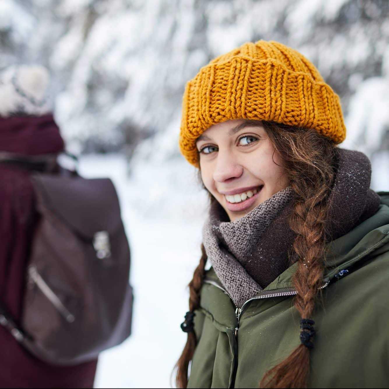 Mädchen lächelt in Kamera in winterlicher Kulisse