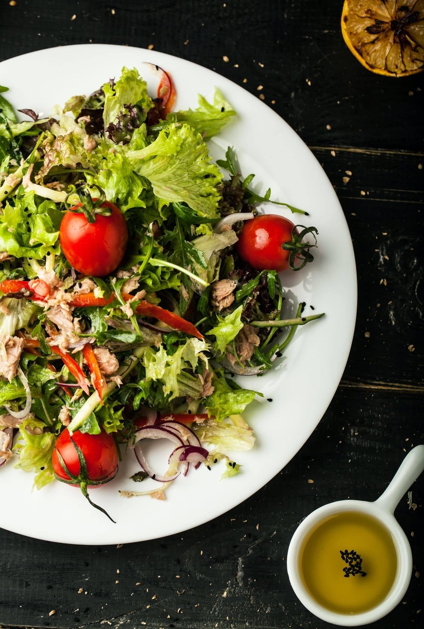 Tasty salad with tuna on dark background